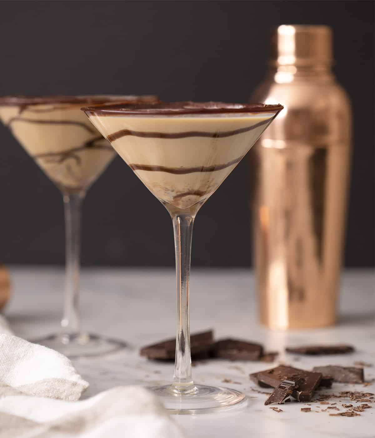 Two chocolate martinis in glasses with swirls of chocolate inside.