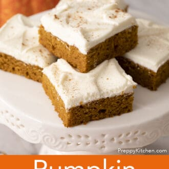 Five pumpkin bars on a small cake stand.