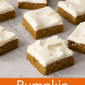 Square pumpkin bars on a marble counter.