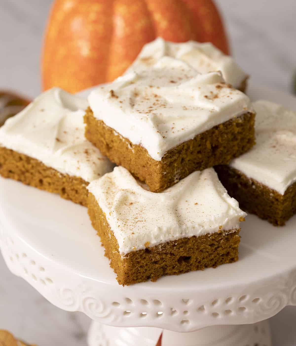 Pumpkin bars on a white cake stand.