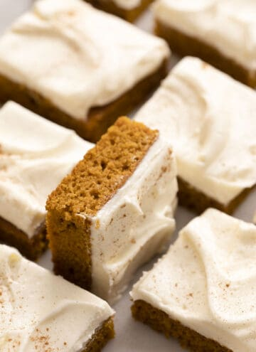Pumpkin bars with cream cheese frosting on a marble counter.