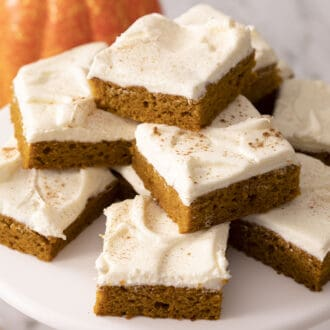 A stack of pumpkin bars with frosting on a cake stand.