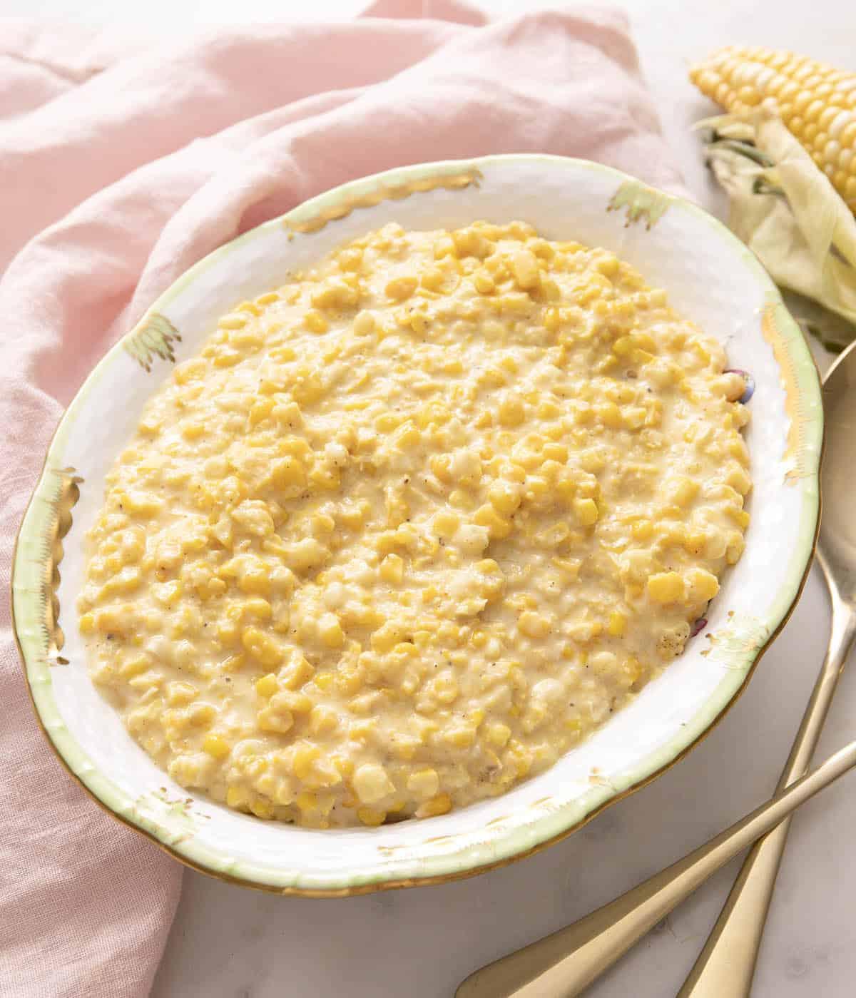 Creamed corn in a porcelain serving bowl.