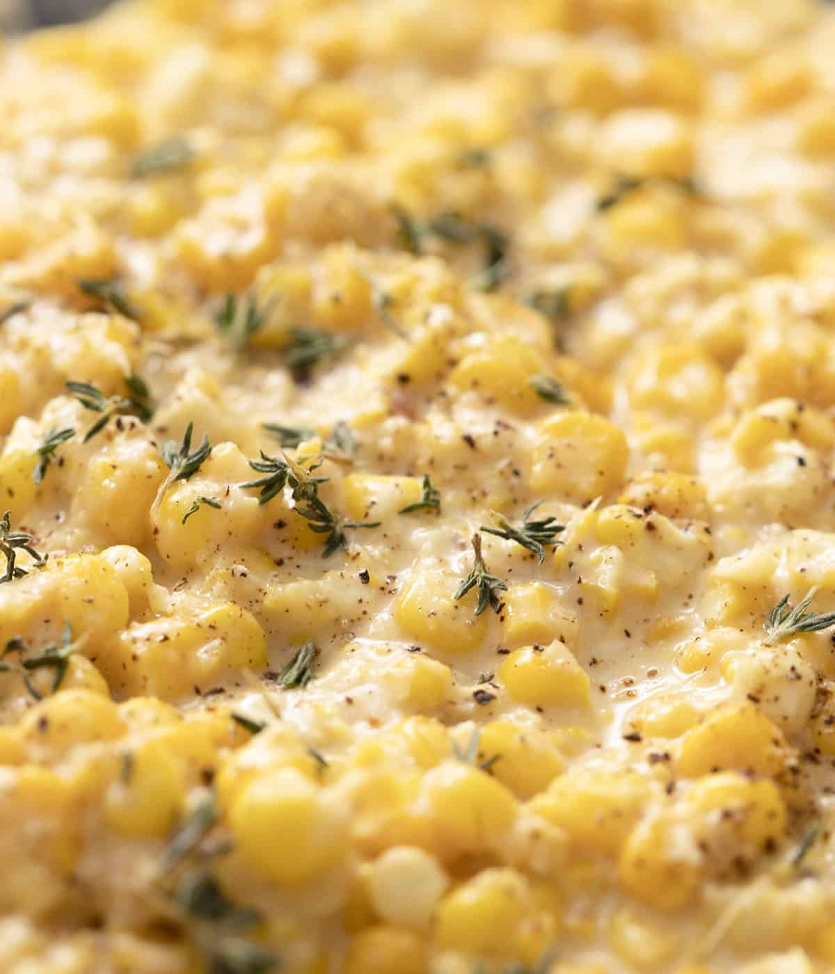 A cloeup photo of creamed corn flecked with thyme and black pepper.
