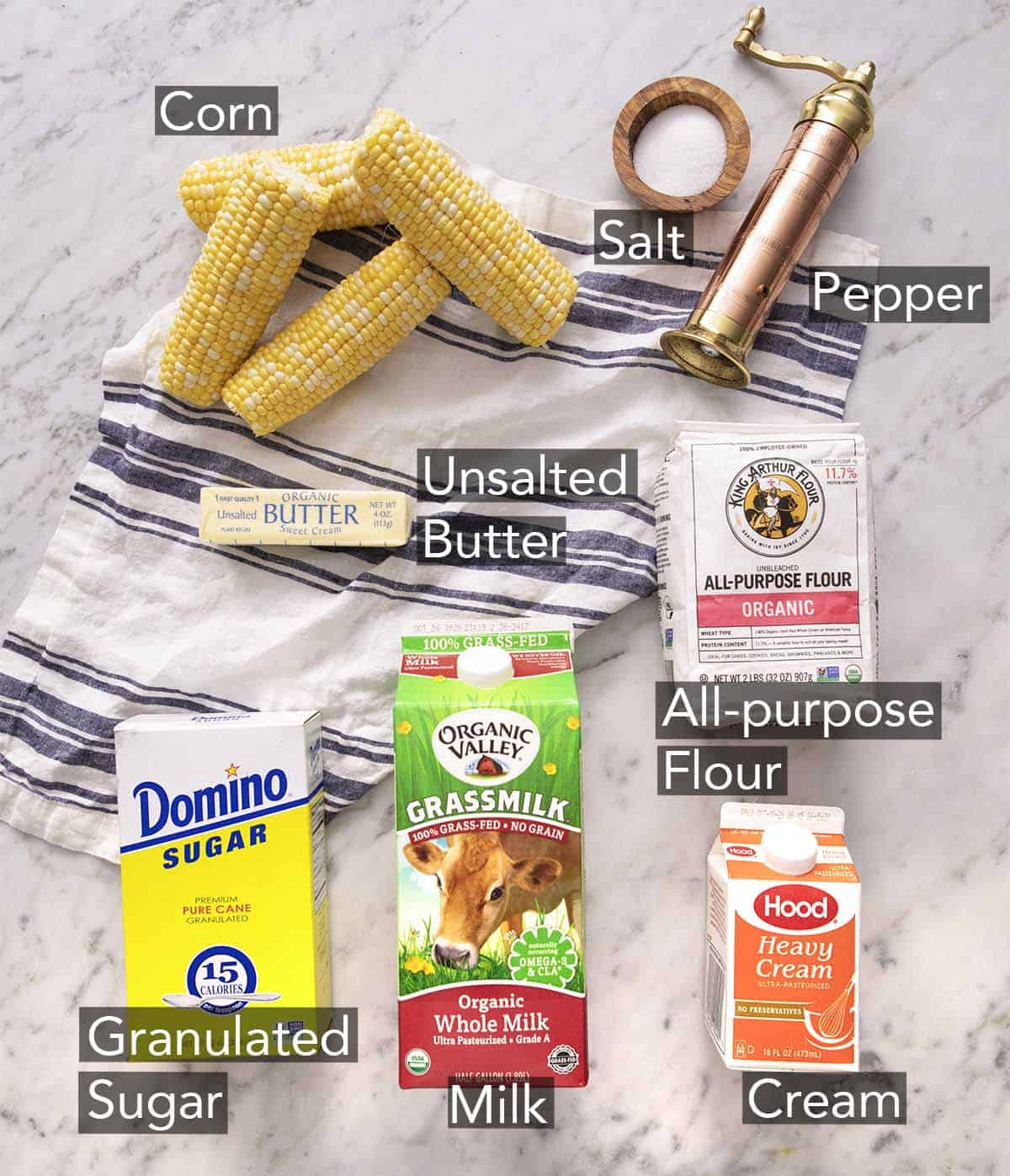 Ingredients to make creamed corn laying on a striped napkin.