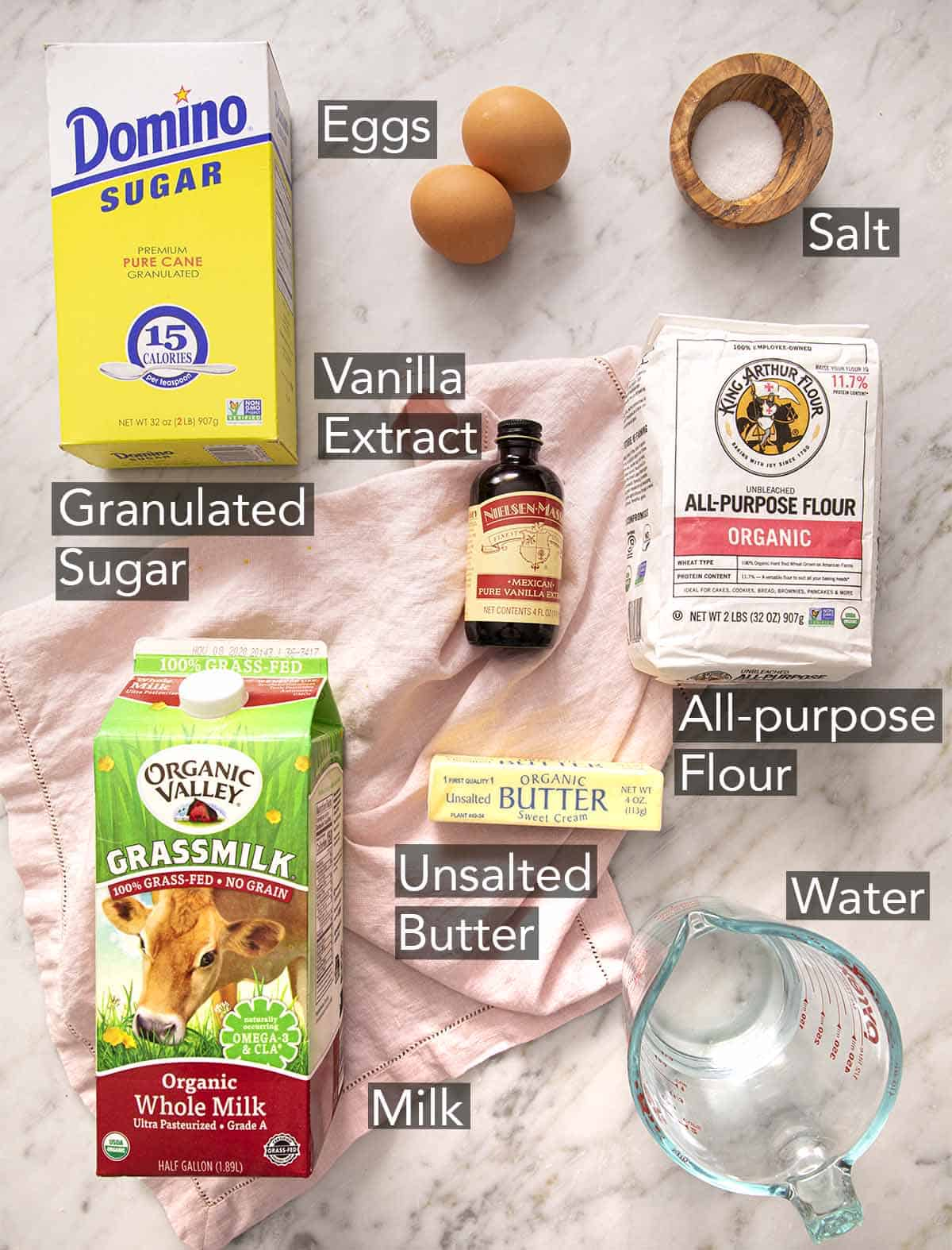 Ingredients to make crepes on a marble counter.
