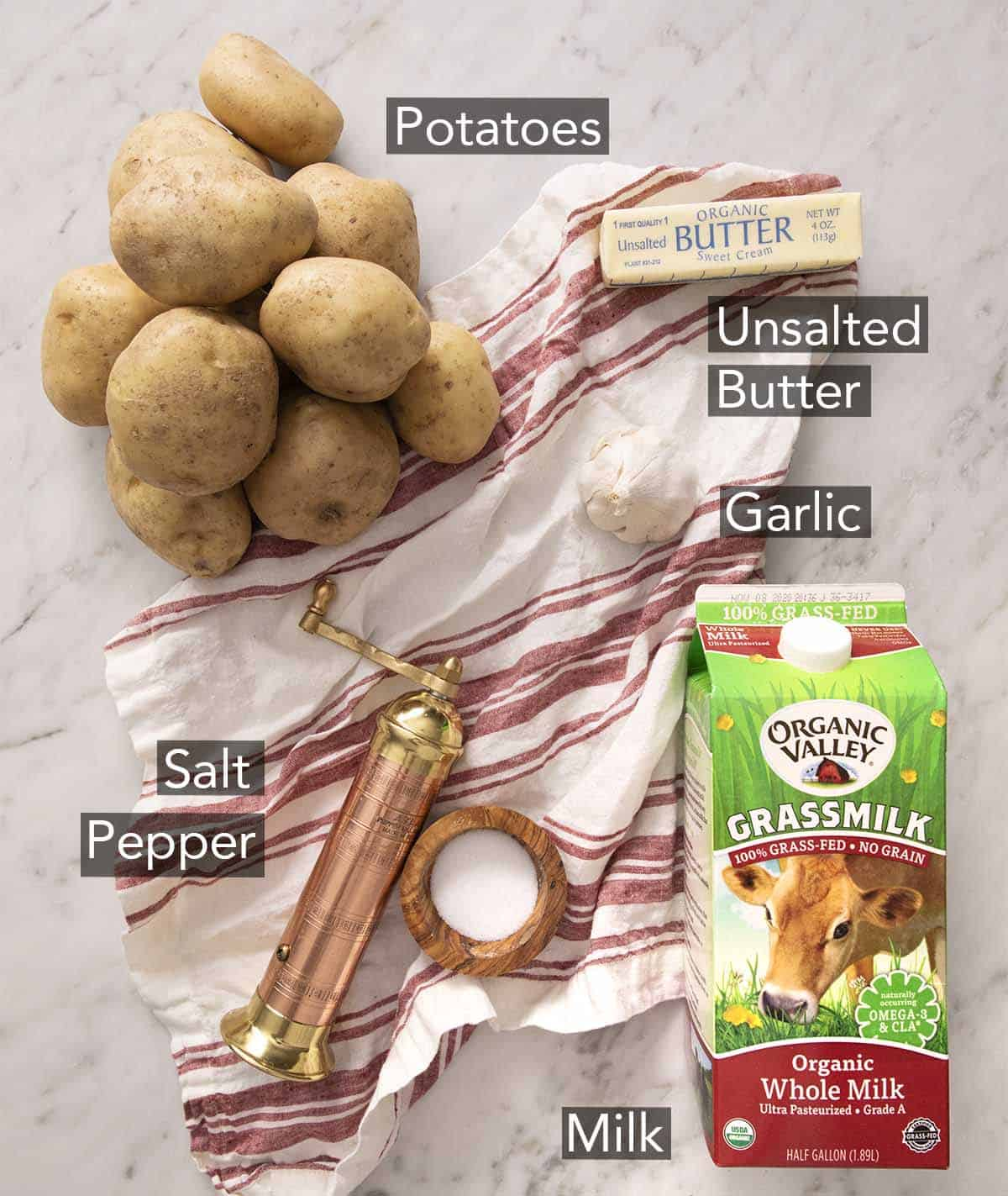 Ingredients to make mashed potatoes on a marble counter.