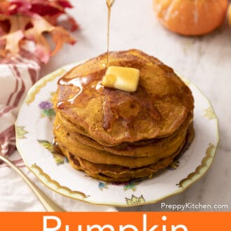 Maple syrup drizzling onto a stack of pumpkin pancakes on a porcelain plate.