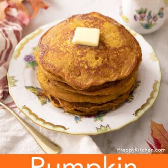 A stack of pumpkin pancakes with butter on a porcelain plate.