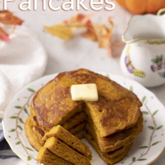A stack of three pumpkin pancakes with a fork holding a piece resting on the plate.