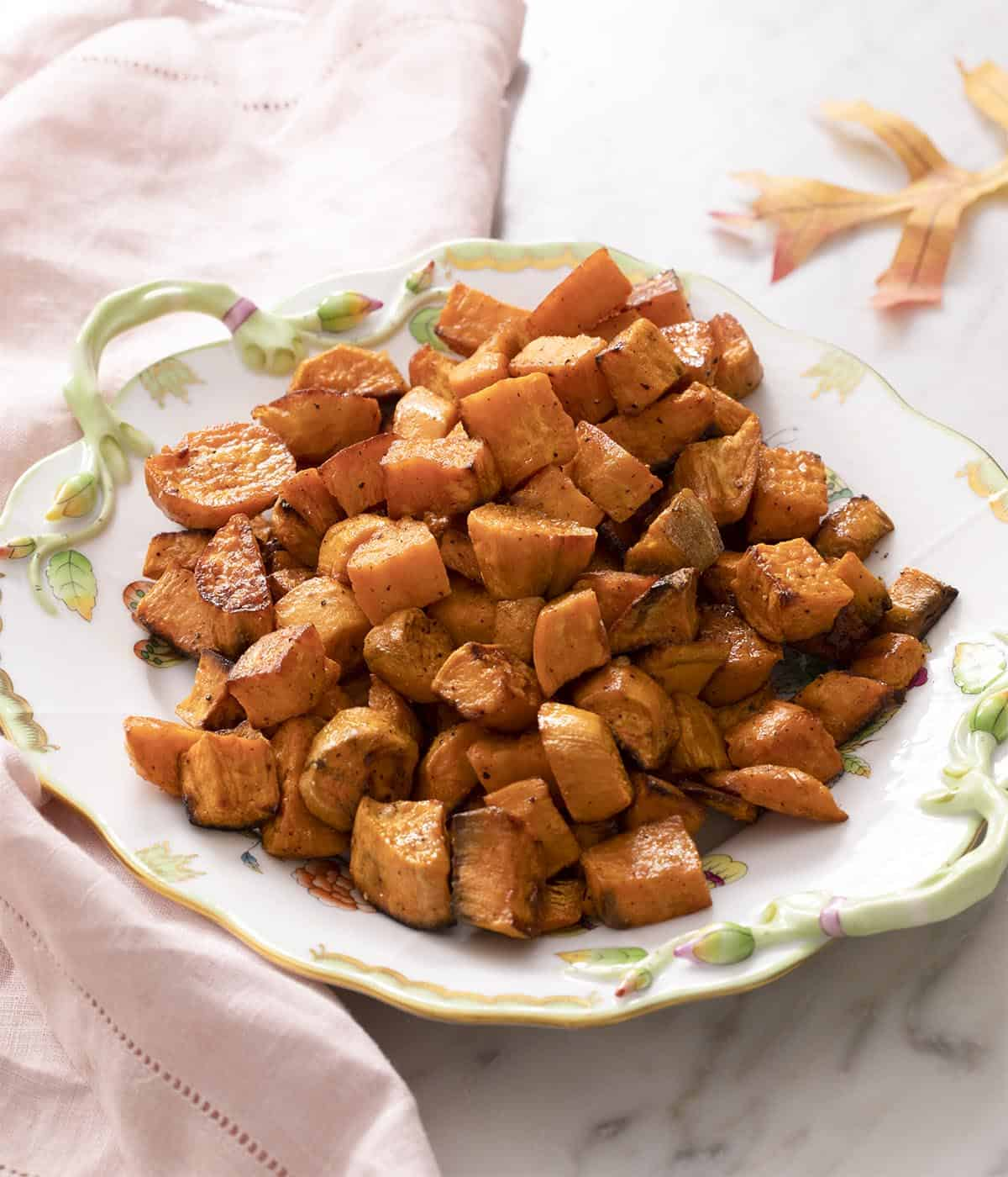 Roasted sweet potatoes on a white serving dish.