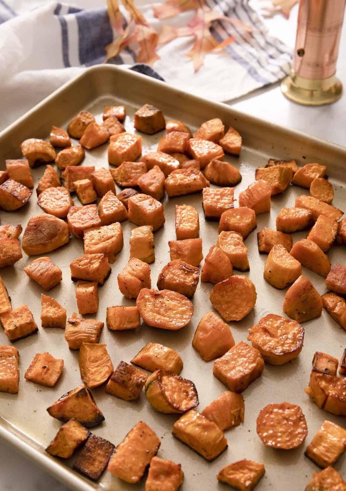 Roasted sweet potatoes on a golden baking sheet.