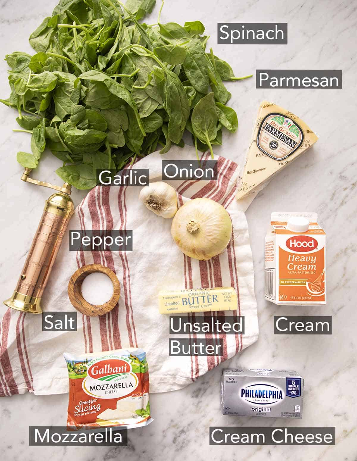 Ingredients to make creamed spinach laying on a marble counter with a striped napkin.