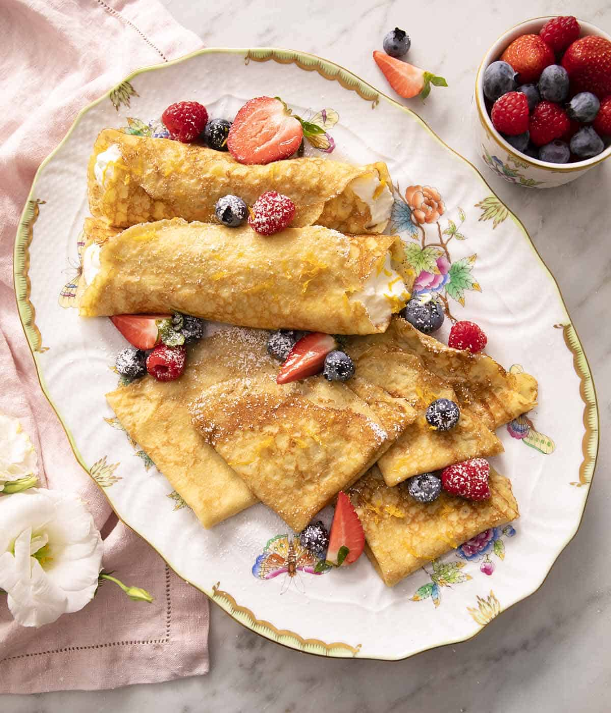 A large platter with crepes and berries on a marble surface.