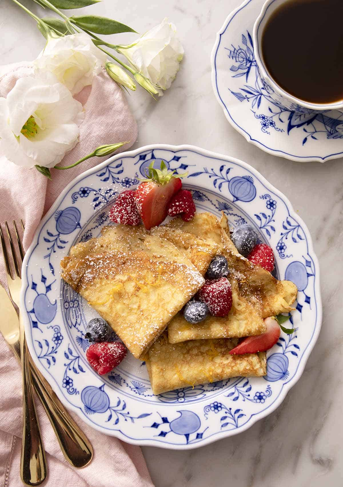 Folded crepes with berries and powdered sugar on a blue and white plate.