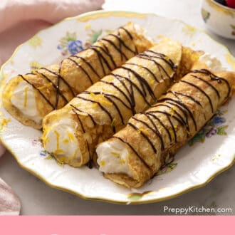 rolled crepes on a plate with chocolate drizzle