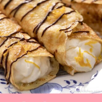 close up of rolled crepes on a plate with chocolate drizzle