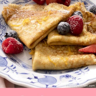 folded crepes on a plate with berries