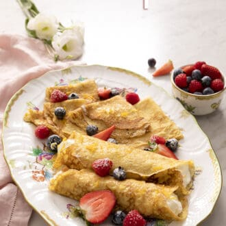 rolled and folded crepes on a platter with berries