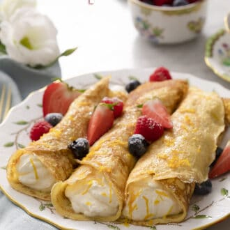 rolled crepes on a plate with berries