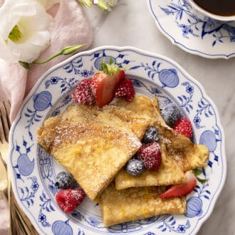 rolled crepes on a blue and white plate with berries