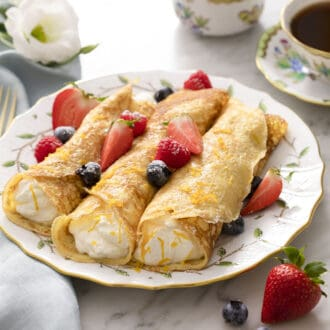 Three crepes filled with whipped cream and berries.