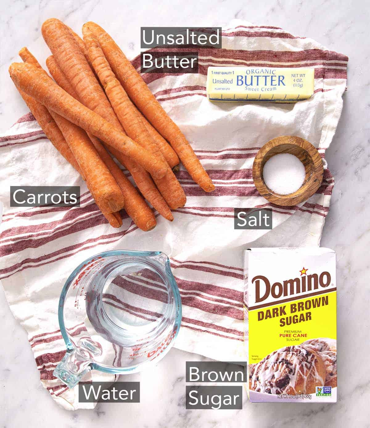 Ingredients to make glazed carrots on a marble counter.