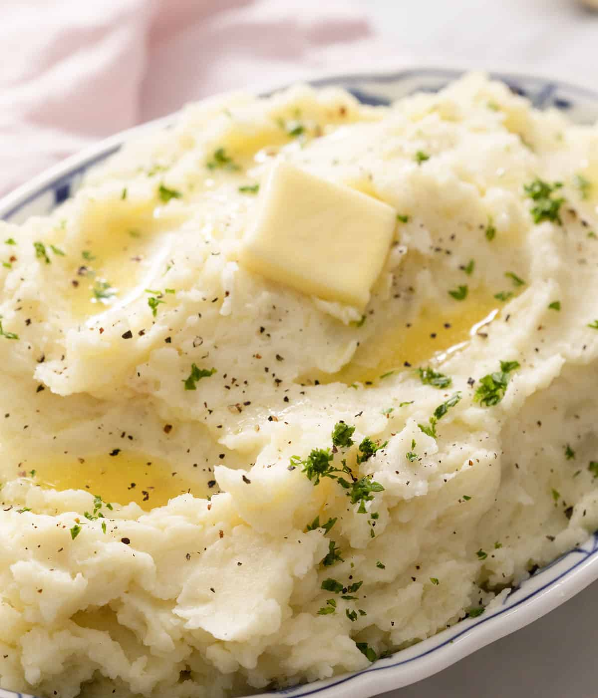 A big serving dish of mashed potatoes with a pat of butter melting on top.