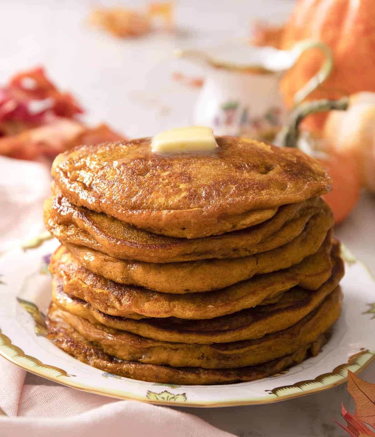 A stack of pumpkin pancakes on a blue and white plate.