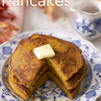A stack of three pumpkin pancakes with a piece cut out.
