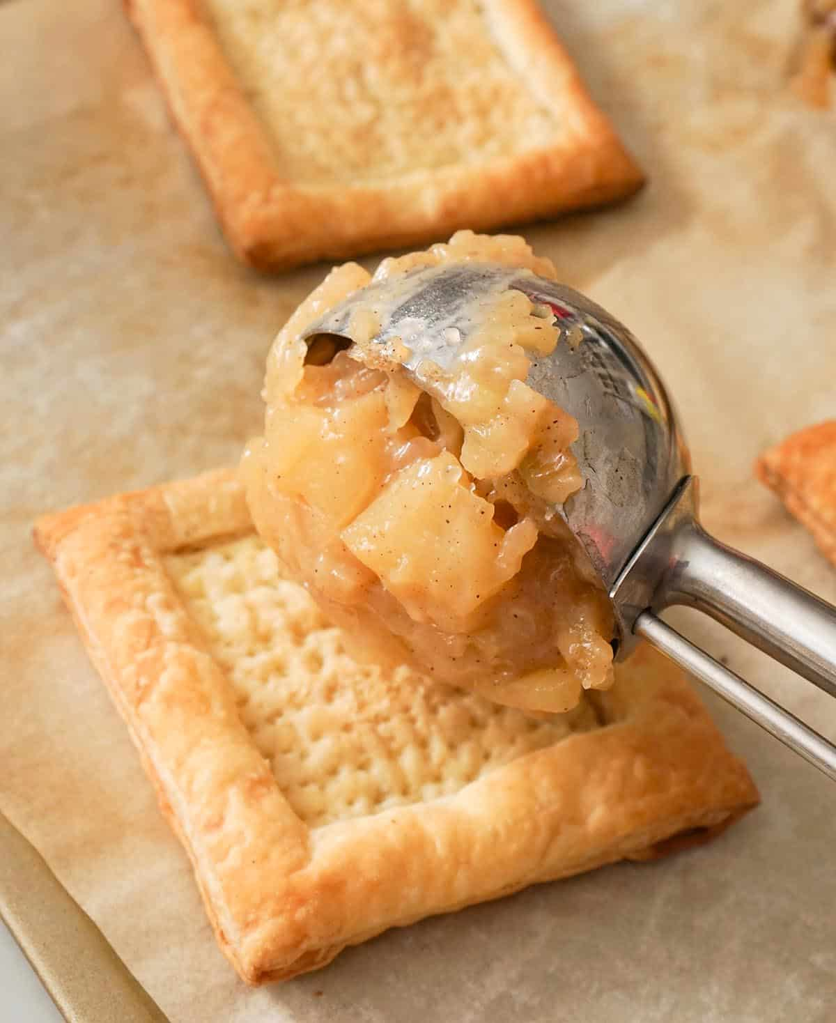 Apple pie filling being added to puff pastry shells.