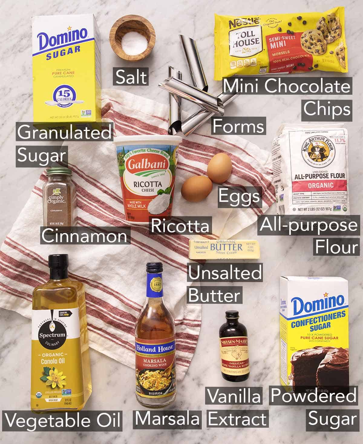 Ingredients to make cannoli on a marble counter.