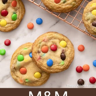several M&M Cookies on a copper cooling rack