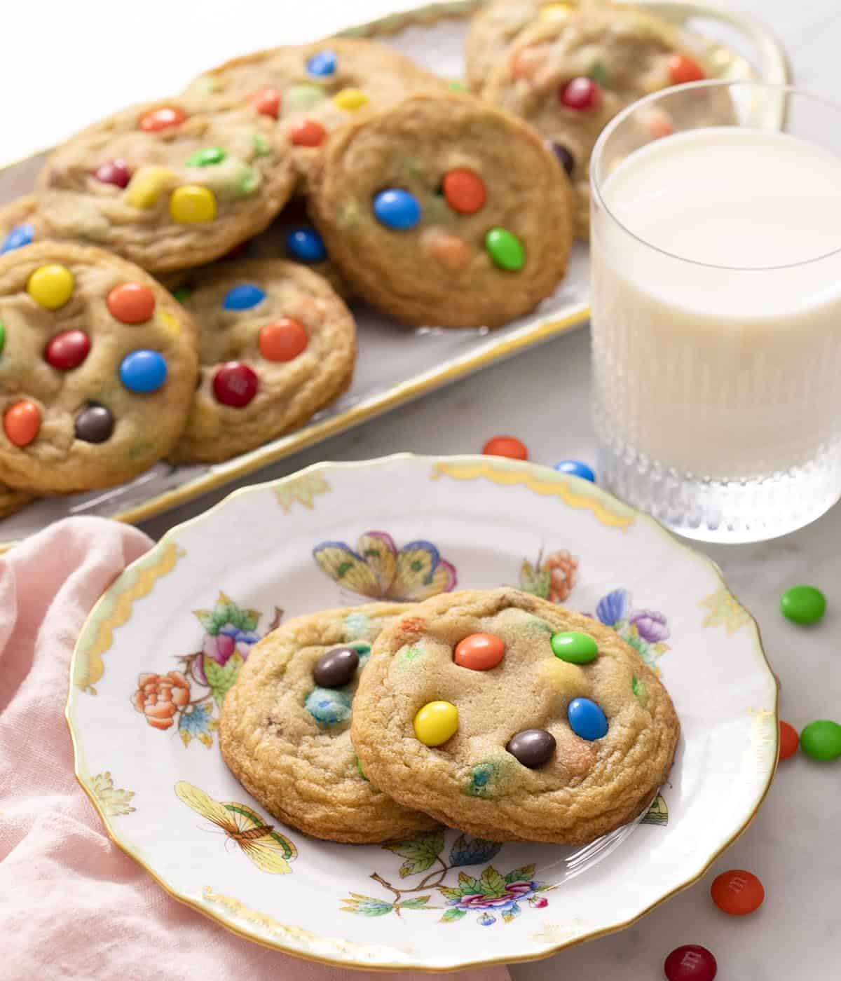 Two M&M cookies on a plate next to a glass of milk.
