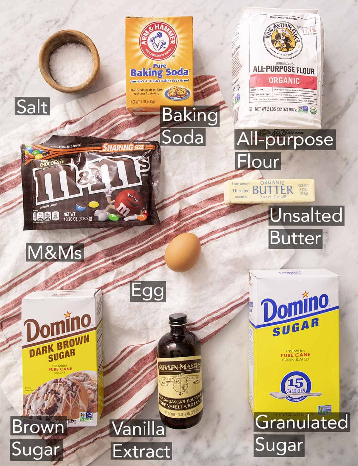 Ingredients to make M&M cookies on a marble counter.
