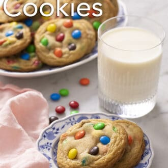 2 M&M Cookies on a blue and white plate with a glass of milk