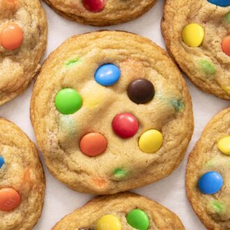 M&M cookies arranged on a sheet of parchment paper.