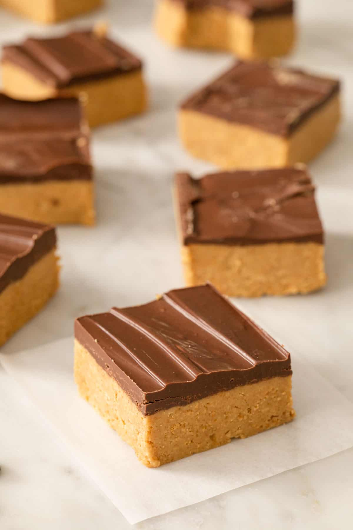 A close up of peanut butter bars on a marble surface