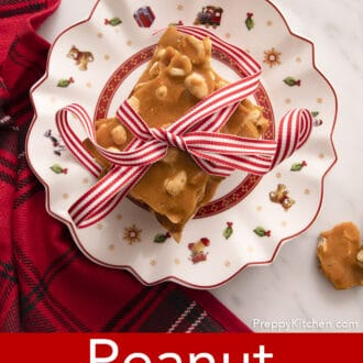 overhead photo of pieces of peanut brittle stacked on a christmas plate