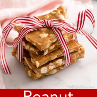 pieces of peanut brittle stacked and tied in christmas ribbon