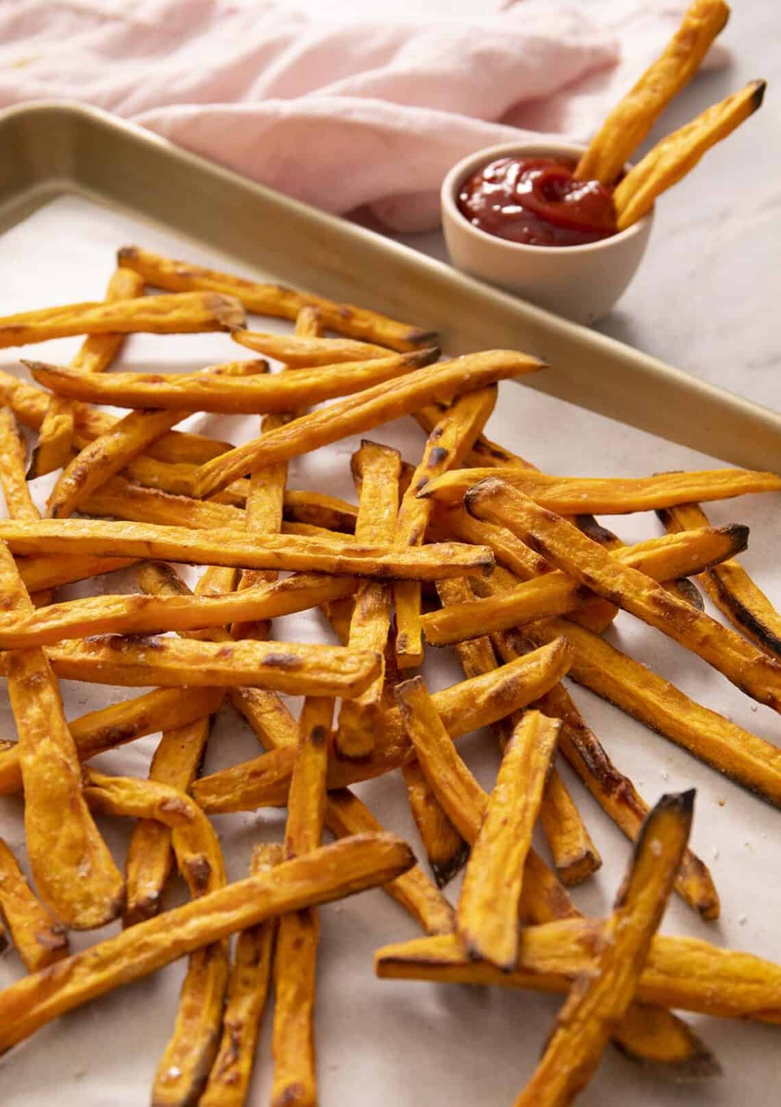 A pile of sweet potato fries on a golden baking sheet.