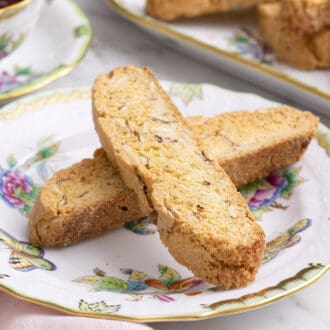 Two almond biscotti on a porcelain plate.