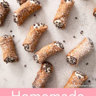 several cannoli sprinkled with powdered sugar spread across white marble counter