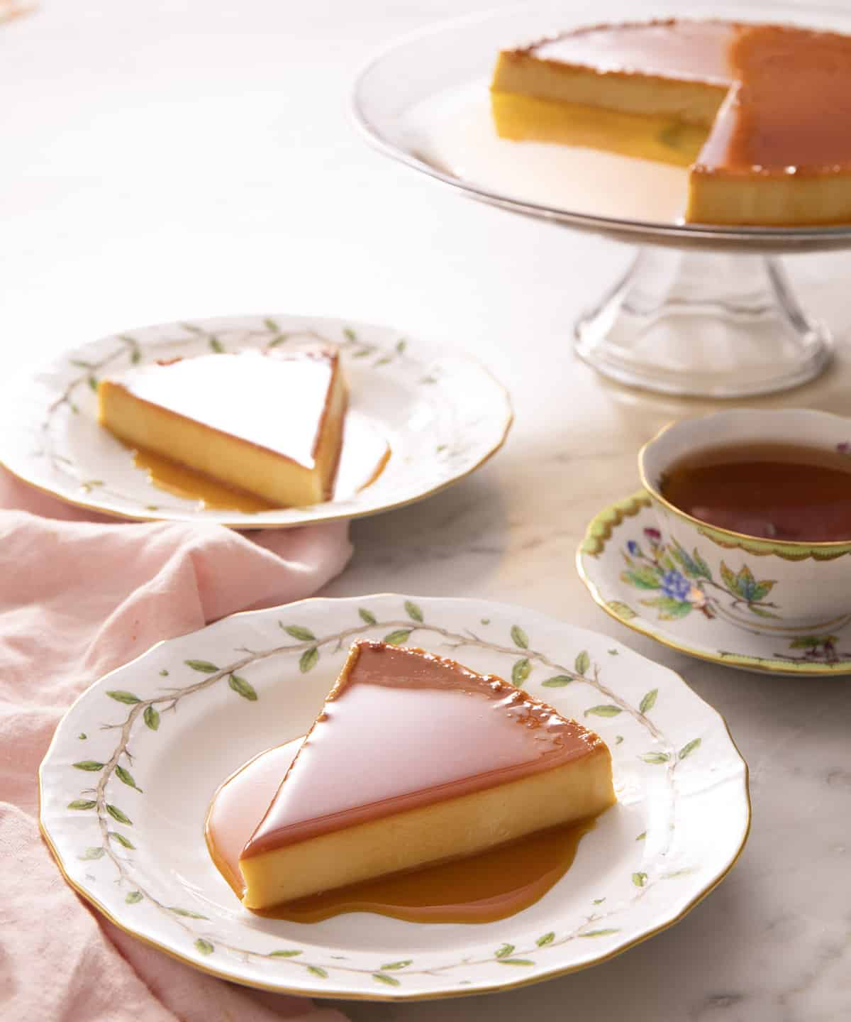 Pieces of flan on porcelain plates next to a cup of tea.
