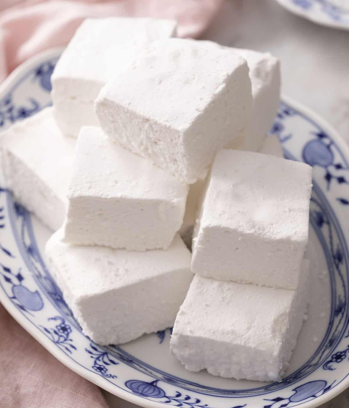 A pile of marshmallows on a blue and white serving dish.