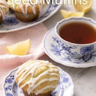 a lemon poppy seed muffin on a blue and white plate with a cup of tea