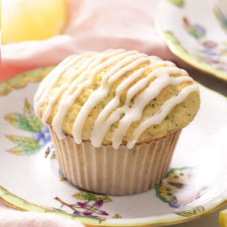A lemon poppy seed muffin with lemon glaze on a small plate.