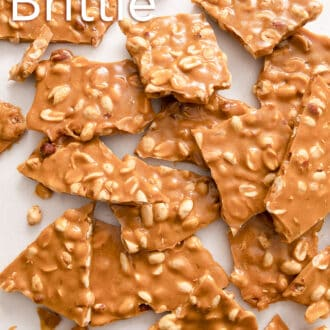 pieces of peanut brittle scattered on a white counter