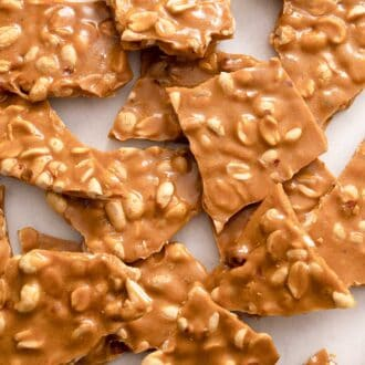 A pile or peanut brittle on a sheet of parchment paper.