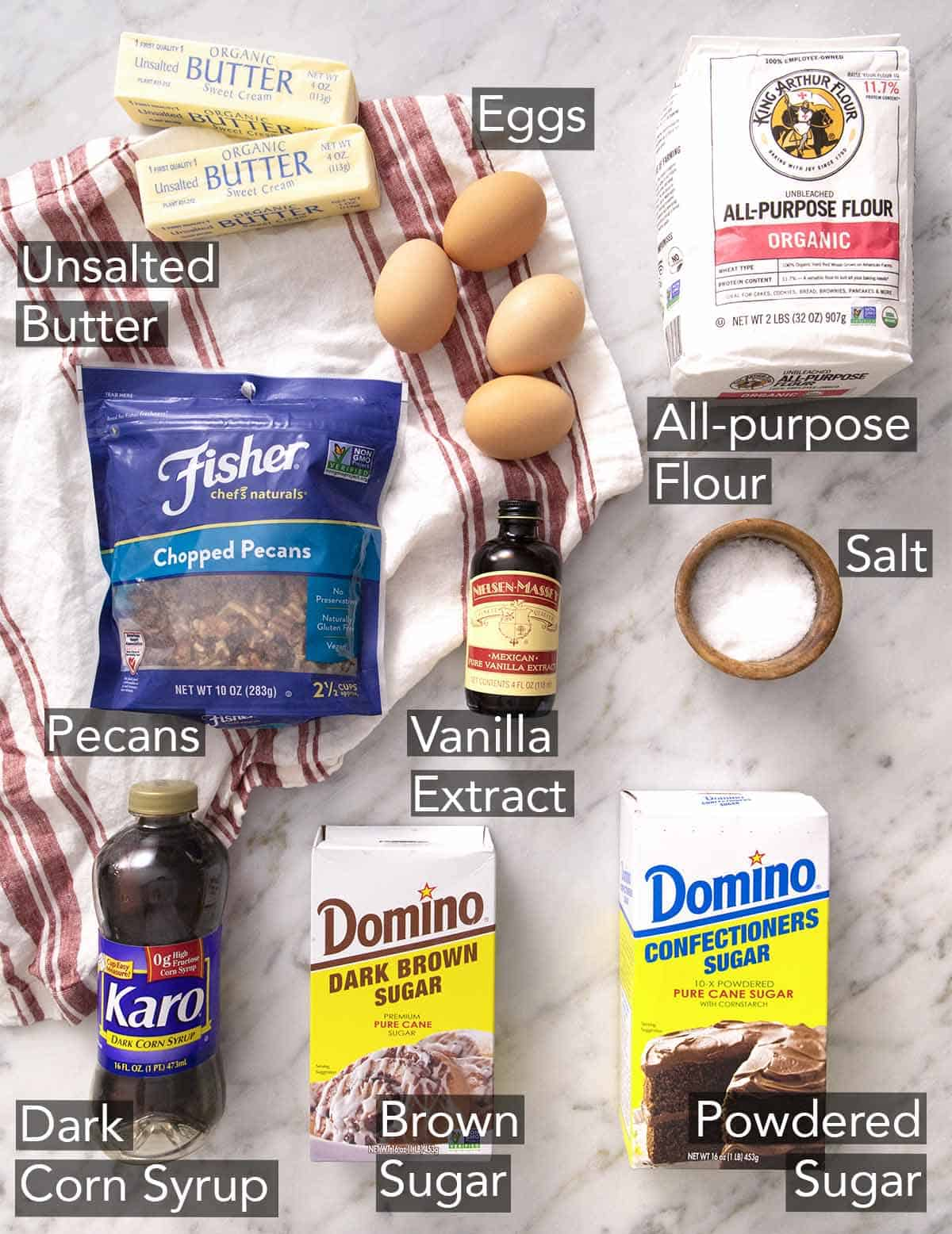 Ingredients to make pecan pie bars on a marble counter.